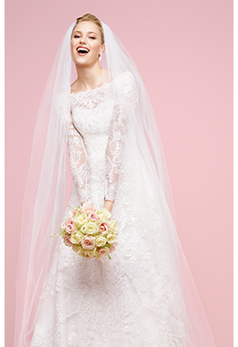 Bride in long sleeve lace dress with flowers