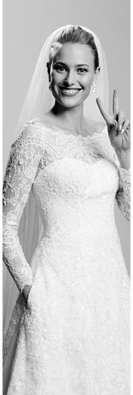 Model in lace wedding dress with veil making peace sign