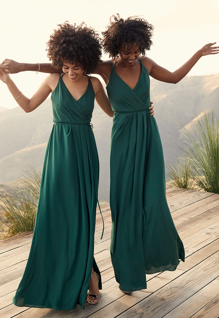 Bridesmaids dancing with arms around each other outside