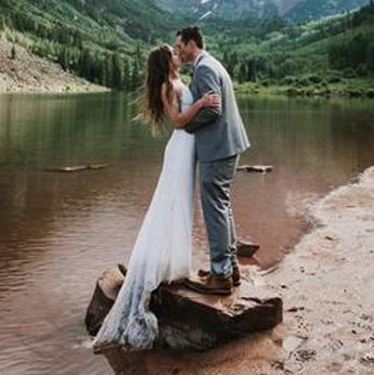 Bride and groom kissing on lakeside rock