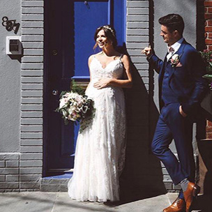 Real bride wearing Melissa Sweet wedding dress in front of a blue door with her groom