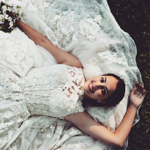 Bride laying down with the back of her dress skirt spread out beneath her
