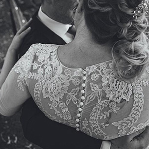 Close up of groom holding bride and showing the detail of her dress