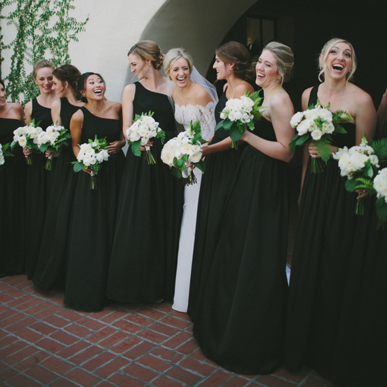 Bride laughing amongst bridesmaids in black holding white and green bouquets