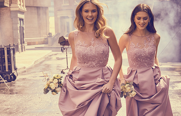 Two bridesmaids in pink dresses running down the street