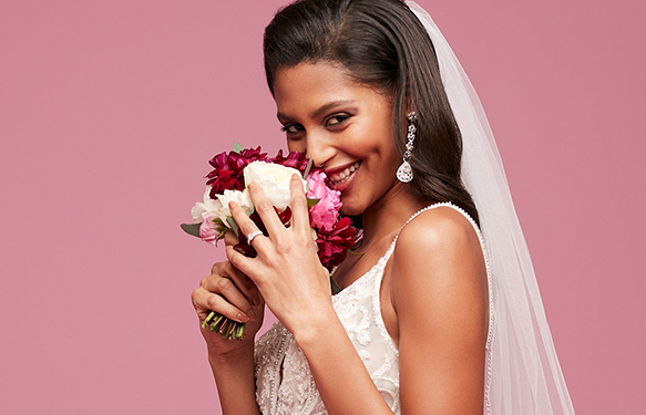 Bride smiling and smelling bouquet on pink backdrop