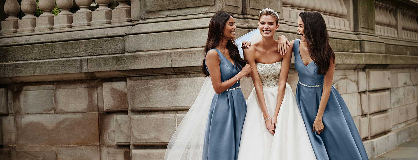 Bride with Bridesmaids next to stone building smiling and laughing