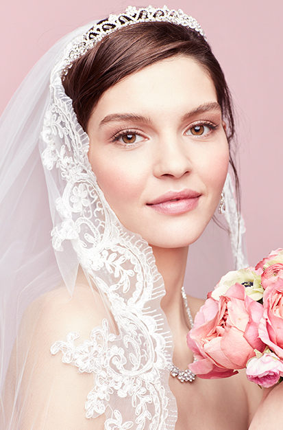 Bride wearing mid height tiara with pearls and crystals with veil