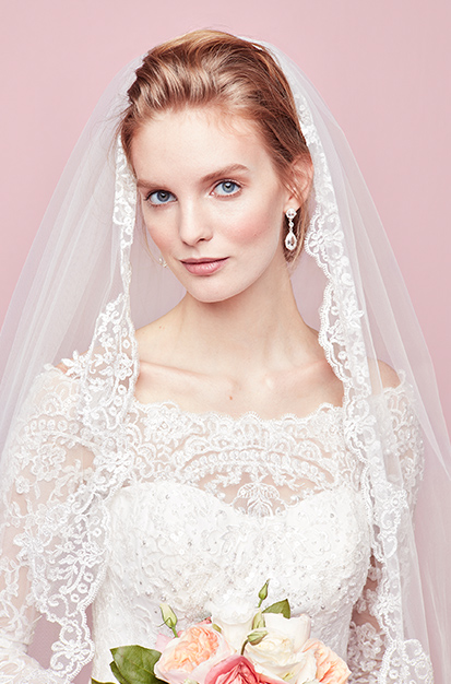 Bride wearing corded lace fingertip veil with sequins