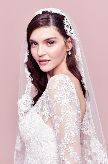Bride wearing hand-sewn lace cathedral veil